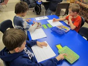 Kindergarten Boys Writing At Table With Crayons
