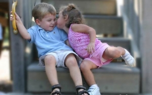 Little Girl Kissing Resistant Little Boy