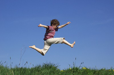 Boy Jumping Over Grass